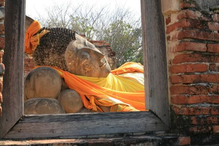 Ornament: reclining Buddha Statue behind window at Wat Putthaisawan in Ayutthaya, Thailand