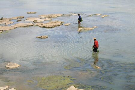 Occupation background  two fishermen holding fish net and walking on shallow water at Kang Sapue, Ubon Ratchathani province, Thailand