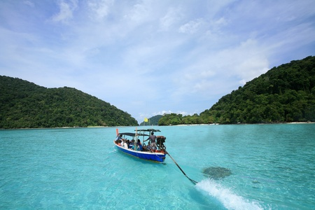 Travel background  long-tailed boat riding on transparent sea against blue sky at Surin islands national park, Thailand Stock Photo - 12689581