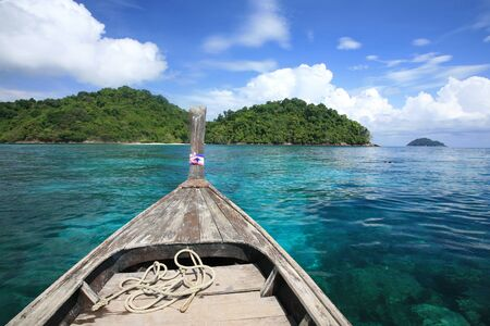 Travel background  head of wooden boat on transparent blue sea at snorkeling spot in Surin islands national park, Thailand 免版税图像