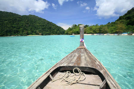 surin: Travel background  wooden boat sailing on transparent blue sea to the coast at Surin islands national park, Thailand Stock Photo
