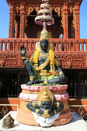 Ornament  black Indra god statue with hand sign in front of red shrine architecture Stock Photo - 13112443