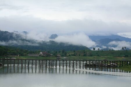 Travel destination  long-tailed boat sailing under Mon wooden bridge against mountain and fog in the morning at Sangklaburi in Kanchanaburi province, Thailand  photo