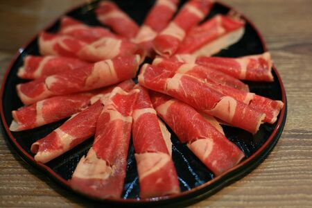 Food background  slices of raw beef on circle black plate in the table for sukiyaki  Stock Photo