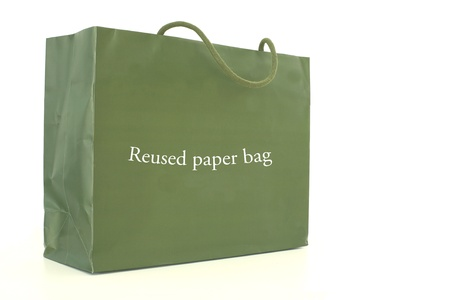 Green paper bag with reused paper bag tag isolated on white background  photo
