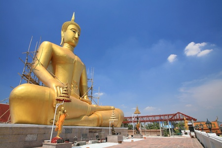 nonthaburi province: Ornament  cross-legged mediation sitting sculpture of large gold Buddha statue against blue sky at wat Bang Chak in Nonthaburi province, Thailand Stock Photo