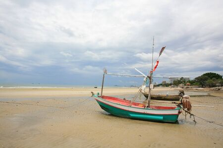 Wooden fishing boats with motor parking on Hua Hin beach in Thailand  photo