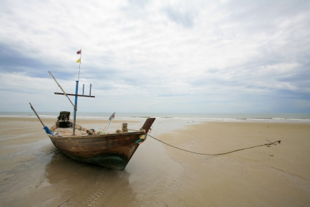 Old wooden fishing boat landing on the beach photo