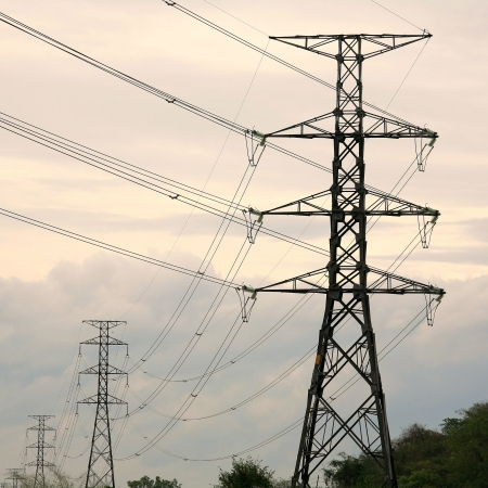 High voltage towers in a row before dusk photo