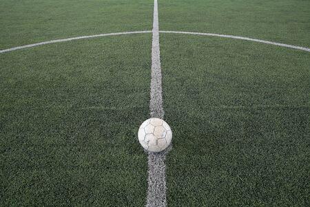 old football at kick off mark on fake grass field photo