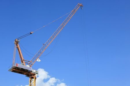jib: Yellow tower crane against blue sky  Stock Photo