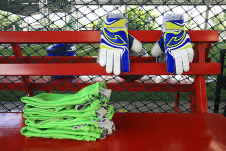 Goalkeeper gloves and soccer shirt bibs on red chair photo