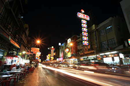 Night View of Bangkok s Chinatown at street with traffic motion, footpath restaurants, and old buildings on June 04, 2012 in Bangkok, Thailand