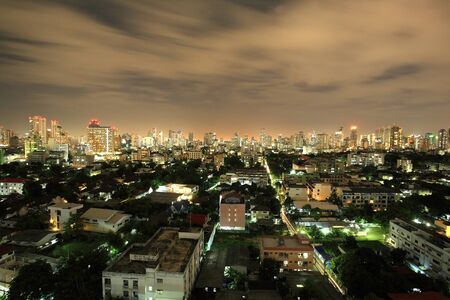 Aerial view of Bangkok cityscape of village, condominiums, and high towers at night  photo