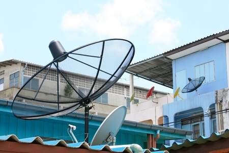 Several satellite dishes attached on building roof and wall  photo