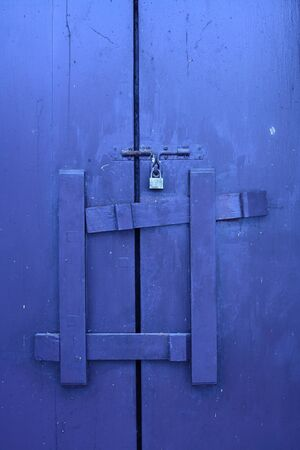Blue wooden door locked by master key and wooden lock Stock Photo - 14421551