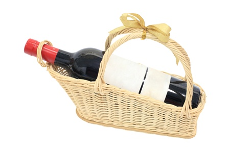 Isolated wine bottle with blank label on present basket with golden ribbon Archivio Fotografico