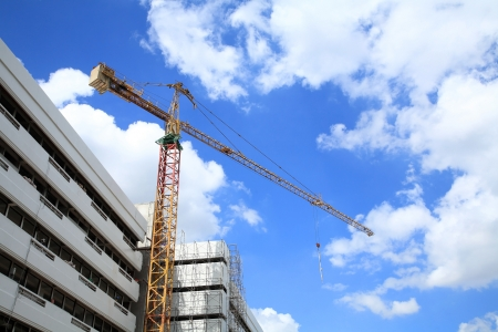 Construction site with big yellow crane against blue sky and cloud Stock Photo