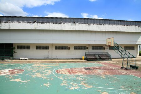 Old outdoor basketball court against blue sky photo
