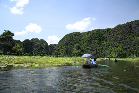 Tam Coc national park  small boats are sailed by sailors  feet to see rice fields , three caves, and limestone mountains along the Ngo Dong river in Ninh Binh, the northern of Vietnam photo