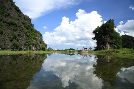 Natural scenic of paddy field, a small pagoda, and mountains along the Ngo Dong river against blue sky at Tam Coc national park in Ninh Binh, the northern of Vietnam  photo