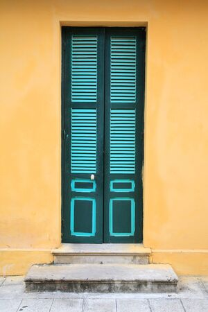 Vintage green door and yellow wall of Ho Chi Minh s Residence in Hanoi, Vietnam photo
