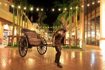 Rickshaw with driver statue decorated at Asiatique in Bangkok, Thailand photo