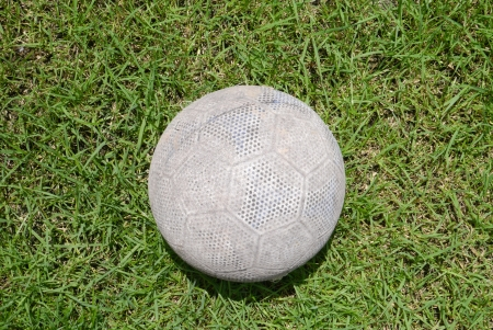 Old small football on the grass photo