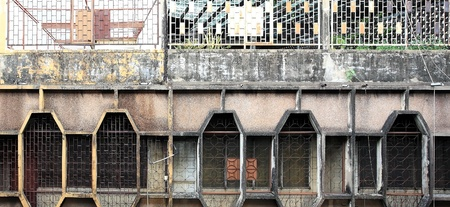 Windows covered by metal lattice at the old building