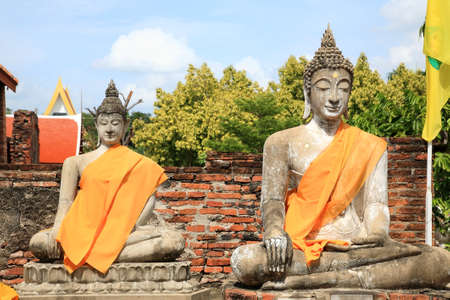 Ancient Buddha status against blue sky at Wat Yai Chaimongkol in Ayutthaya, Thailand photo