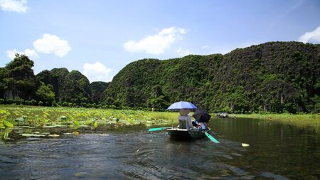 Boats are sailed by sailors  feet to see rice fields along the Ngo Dong river at Tam Coc in Ninh Binh, the northern of Vietnam photo