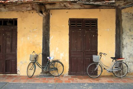 Two Bicycles parking near the doors and wall photo