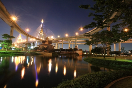 Night scene of a park under King Bhumibol bridge with reflection on the pond in Bangkok, Thailand photo