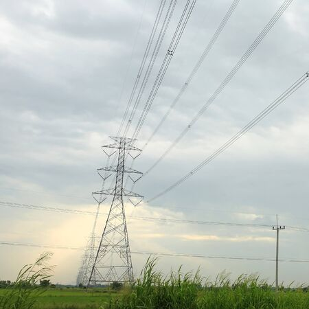 light transmission: High voltage transmission towers at the grass field with light through the cloud