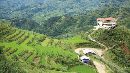 Landscape of building tower and green terraced rice fields on the mountain at Cat Cat village in Sapa, Vietnam photo
