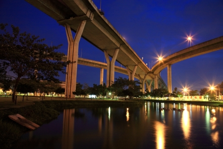 King Bhumibol bridge above park with reflection on the pond at night  photo