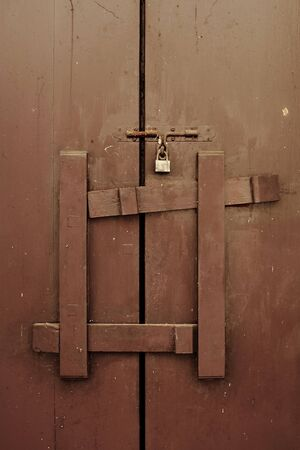 Brown wooden door locked by master key and wooden logs photo