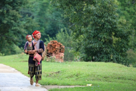 SAPA-JUL 23  Unidentified hill tribe mother with her son walks down from the Red Dao Minority village on July 23, 2012 in Sapa, Vietnam  Red Dao Minority are the 9th largest ethnic group in Vietnam