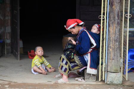 SAPA-JUL 23  Unidentified hill tribe mother takes care her sons and sews textile at the Red Dao Minority village on July 23, 2012 in Sapa, Vietnam  Red Dao are the 9th largest ethnic group in Vietnam