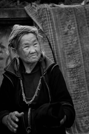 SAPA - JUL 22  Unidentified Black Hmong s woman from Cat Cat village sells textile on July 22, 2012 in Sapa downtown, Vietnam  Since Cat Cat closes to Sapa, many tribes walk to Sapa to sell souvenirs