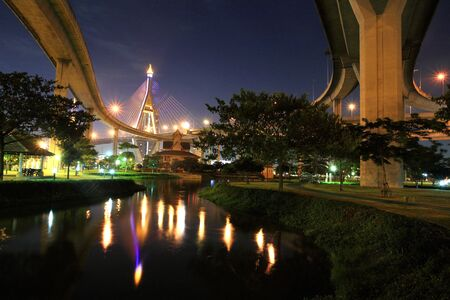 King Bhumibol Bridge above the park with reflection on the pond in Bangkok, Thailand photo