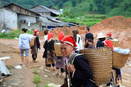 SAPA-JUL 23  Unidentified Red Dao hill tribes and visitors walk together to visit the village on July 23, 2012 in Sapa, Vietnam  Red Dao Minority are the 9th largest ethnic group in Vietnam