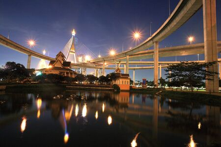 King Bhumibol bridge above a park with reflection on the pond at night in Bangkok, Thailand photo