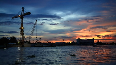 Tower crane near Chao Phraya river at dusk in Bangkok, Thailand photo