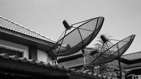 Two satellite dishes mounted on the roof photo