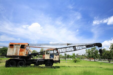 Old truck with digger on the grass against blue sky photo