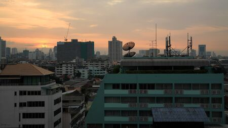 high frequency: Telecommunications antennas on top of building against sunset