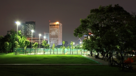 night landscape: Outdoor sport stadium at State Railway Public Park, also called  Suan Rot Fai  against modern buildings at twilight in Bangkok, Thailand Stock Photo
