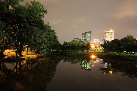 Night scene of State Railway Public Park, also called  Suan Rot Fai, against modern buildings at twilight with reflection on the pond in Bangkok, Thailand photo