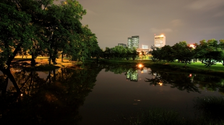 Night view of State Railway Public Park, also called  Suan Rot Fai, against modern buildings at twilight with reflection on the pond in Bangkok, Thailand photo